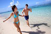 Casal correndo numa praia