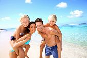 image of piggyback ride  - Family of four having fun at the beach - JPG