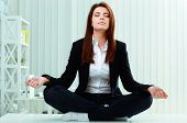 Young beautiful businesswoman meditates on the table in office