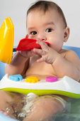 Baby boy bathes in a small bathtube with colored toys
