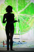 Silhouette of female body standing in studio with painted wall, focus on the wall.