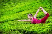stock photo of natarajasana  - Yoga natarajasana dancer pose by woman in red costume close up on tea plantations in Munnar Kerala India - JPG
