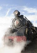 stock photo of locomotive  - Vintage steam locomotive letting off steam at station - JPG