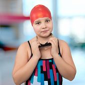Portrait Of A Young Girl In A Red Cap At The Pool.