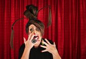 foto of drag-queen  - Shouting drag queen with ponytails with hands in front of mouth - JPG