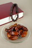 Composition with holy book,rosary and dates palm, on gray background
