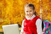 stock photo of 11 year old  - Close portrait of happy blond 11 years old girl with amazing smile sitting on the bench with laptop doing homework outside in the autumn park on sunny day - JPG