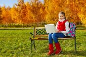 stock photo of 11 year old  - Happy blond 11 years old girl with amazing smile sitting on the bench with laptop doing homework outside in the autumn park on sunny day - JPG