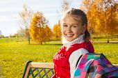 pic of 11 year old  - Close portrait of happy blond 11 years old girl with amazing smile turning back sitting on the bench in the autumn park on sunny day - JPG