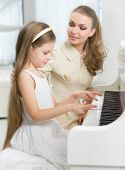 Master teaches little girl to play piano. Concept of music study and arts