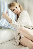 foto of legs apart  - Beautiful and sexy young adult sensuality blonde woman in blue lingerie and brown sweater on the white sofa in window on luxury apartment - JPG
