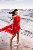 stock photo of naturist  - Young naked woman on a beach with red fabric - JPG