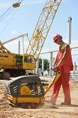 stock photo of vibration plate  - builder worker compacting soil with vibration plate compaction machine during pavement roadwork - JPG