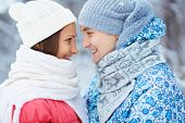 Portrait of happy young woman and her boyfriend in winterwear looking at one another