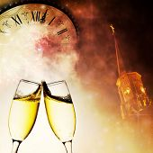Champagne glasses, church steeple with clock and fireworks in the night