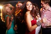 stock photo of brunette  - Portrait of cheerful girl with champagne flute dancing at party while smiling at camera - JPG