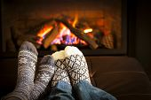 stock photo of flames  - Feet in wool socks warming by cozy fire - JPG