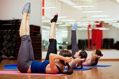 stock photo of rep  - Group of young women working out and strengthening their abs at a gym - JPG