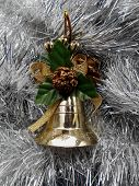 Christmas and New Year decoration bell on a background of silver tinsel