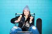 picture of hooligan  - Young funky hipster woman eating ice cream over blue brick wall - JPG