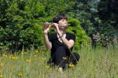 picture of musical instruments  - Female flute player is immersed in her music as she sits on a hillside among the wildflowers - JPG