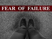 Businessman standing on asphalt starting line with word fear of failure