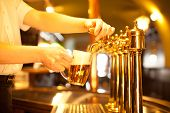 image of spigot  - waiter is drafting a beer from a golden spigot