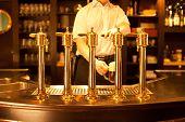 image of spigot  - waiter is drafting a beer from a golden spigot - JPG