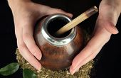 Woman hands holding calabash and bombilla with yerba mate isolated on black