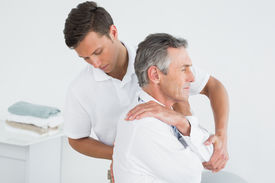 stock photo of chiropractor  - Side view of a male chiropractor examining mature man at office - JPG