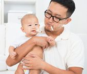 Asian family at home. Bad father smoking with baby together. Cigarette with lit and smoke. Unhealthy lifestyle or stop smoking concept photo.
