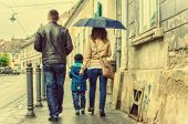 Mother, Father And Child Walking Together On A Rainy Day