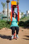 Woman Doing Fitness Training On A Butterfly Outdoor Machine