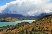 Cold summer in Chile. The National Park Torres del Paine - the emerald waters of the Rio Serrano and snowy peaks  Los Cuernos