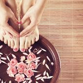 Beautiful legs, flowers, petals and ceramic bowl. Summer spa background.