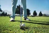 Closeup of golfer with iron hitting tee shot