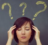 Woman With Headache On Background Of Question Marks