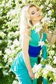Portrait of a beautiful young blonde woman with long hair in a long blue dress