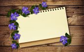 Notepad And Periwinkle Flowers