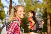 Hiking woman portrait smiling happy in forest. Female hiker girl trekking wearing backpack outside l