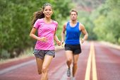 Running young mixed race couple training for marathon outside on road. Happy smiling beautiful mixed