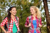 Healthy lifestyle women laughing hiking walking forest doing outdoor activity having fun together. Multicultural group, Caucasian and Asian girls hikers.