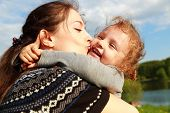 Beautiful Mother Kissing Happy Laughing Kid Girl Outdoors Summer Background