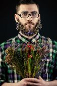 Handsome young man in spectacles and a beard of flowers. Black background.