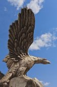 Stone Statue Of A Bird Eagle On A Background Of Blue Sky