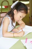 Chinese girl learning to write in kindergarten with a pen at a table