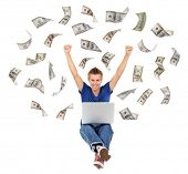 Young man working on laptop with money rain isolated on white