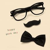 a pair of glasses, a mustache, a bow tie and the sentence happy geek day on a beige background