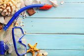Diving goggles,snorkel and seashell on wooden background