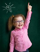 Happy kid girl in glasses with bright idea standing near school blackboard in classroom
